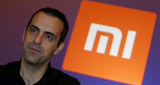 Xiaomi's Vice President Hugo Barra looks on in front of the company's logo during a group interview after the launching ceremony of Redmi Note 3 in Hong Kong